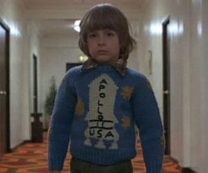 """Kadr z filmu """"Lśnienie"""" w którym główny bohater ma na swetrze rakietę z napisem Apollo 11!"""